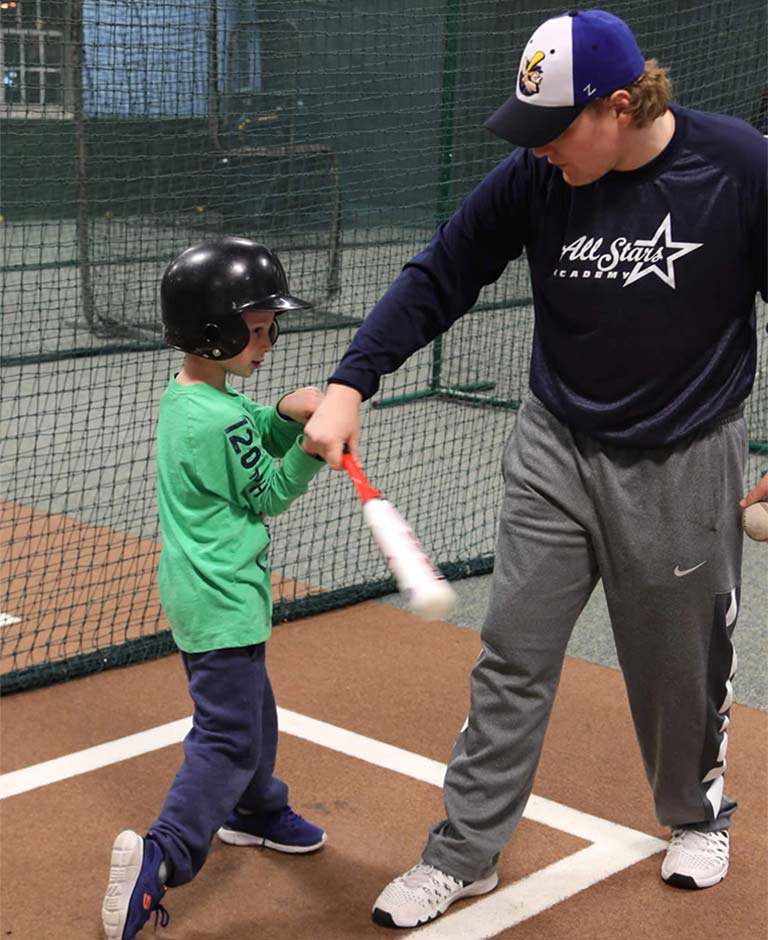 Matt Frey instructing kid on swinging bat