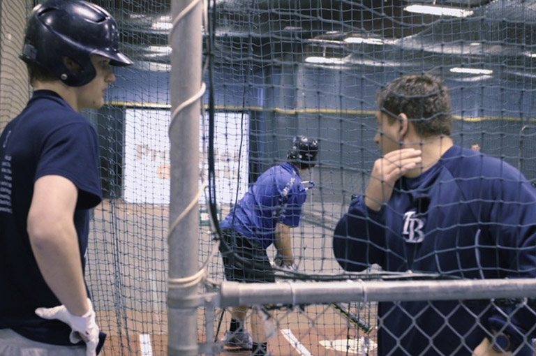 Baseball players inside batting cage