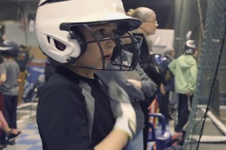 Kid wearing batting helmet