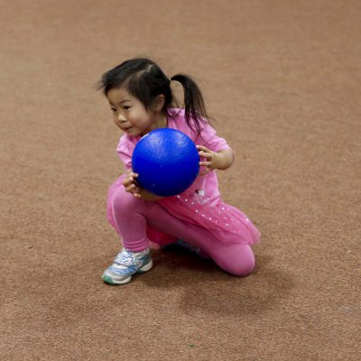 Young child holding blue dodgeball