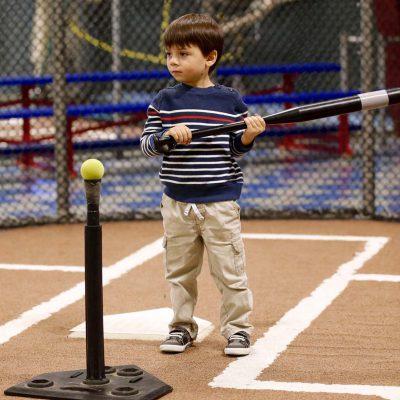 Boy swinging bat at tee-ball