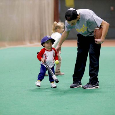 Instructor teaching child to hit